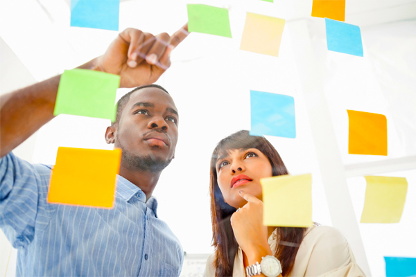 young man and woman looking at post it notes on a clear wall